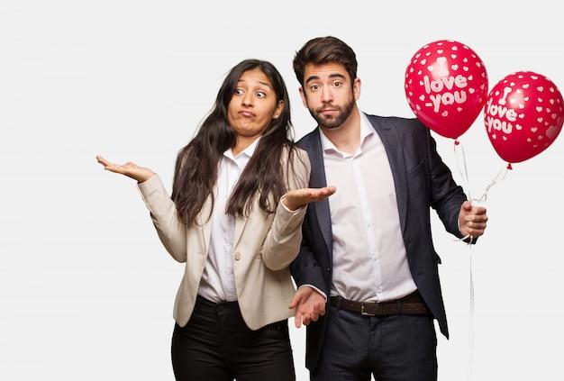 Jeune couple en saint valentin doutant et haussant les épaules