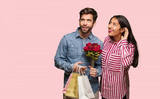 Jeune couple en saint valentin essayer d'écouter un potin