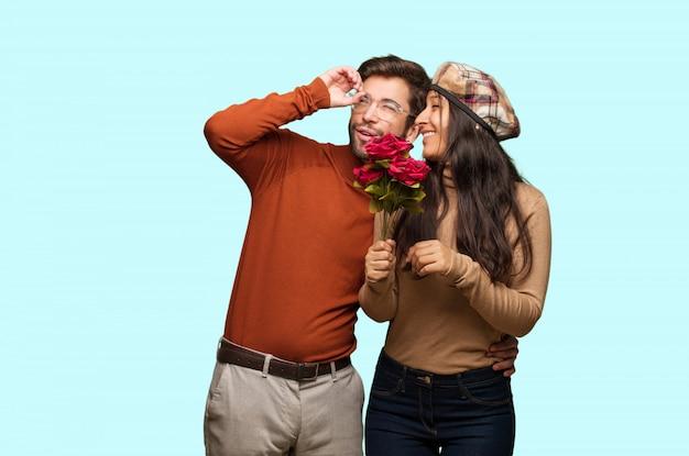 Jeune couple en saint valentin faisant le geste d'une longue-vue