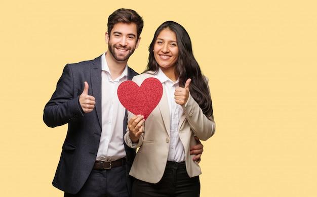 Jeune couple en saint valentin souriant et levant le pouce vers le haut