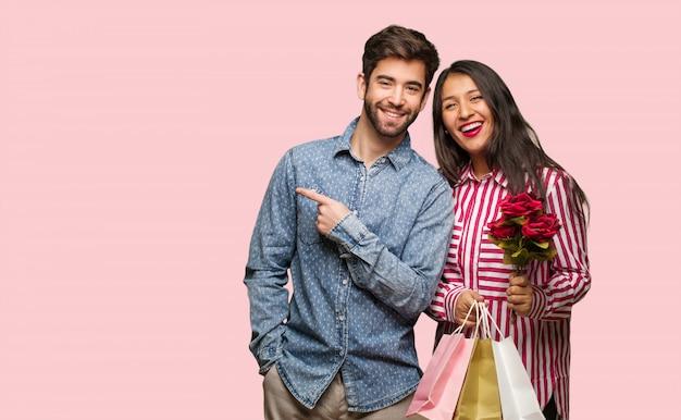 Jeune couple en saint valentin souriant et pointant sur le côté