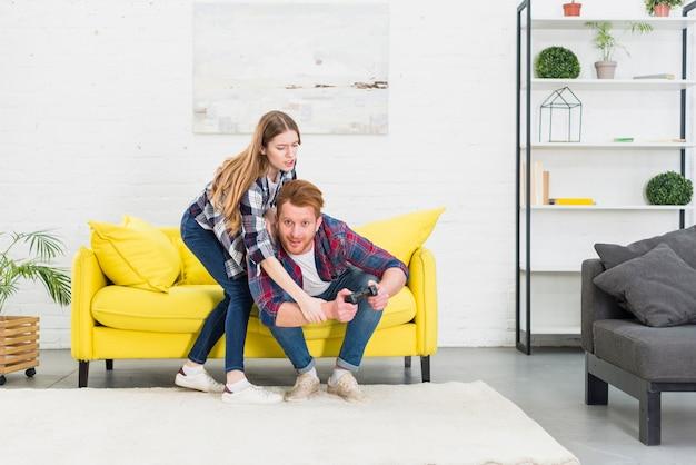 Jeune couple se battant pour une manette de jeu tout en jouant à des jeux vidéo à la maison