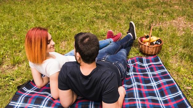 Jeune couple se détendre au pique-nique dans le parc
