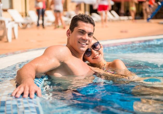 Jeune couple se détendre et regarder la caméra et souriant.