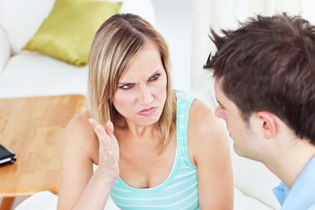 Jeune couple se disputant dans son salon
