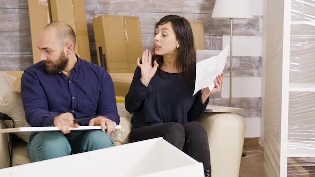 Jeune couple se disputant lors de l'assemblage de meubles dans leur nouvel appartement. instructions de lecture de couple.