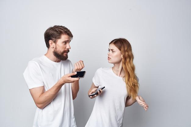 Un jeune couple se dispute la jalousie téléphone fond clair de communication