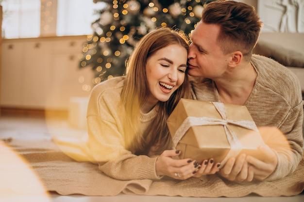Jeune couple se faisant des cadeaux par l'arbre de noël
