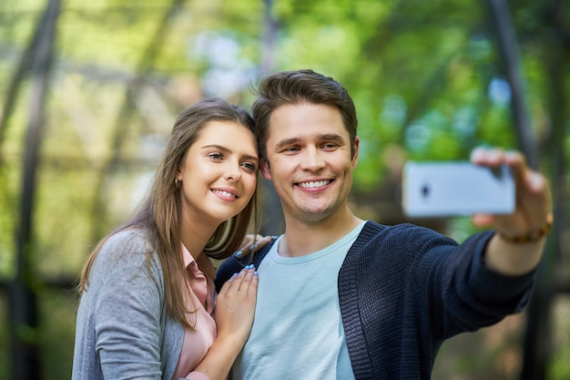 Jeune couple se promenant dans le parc et prenant des photos