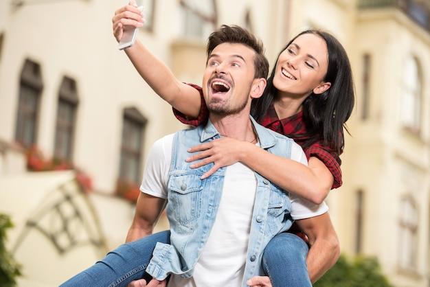 Jeune couple se promène dans la ville et prend une photo.