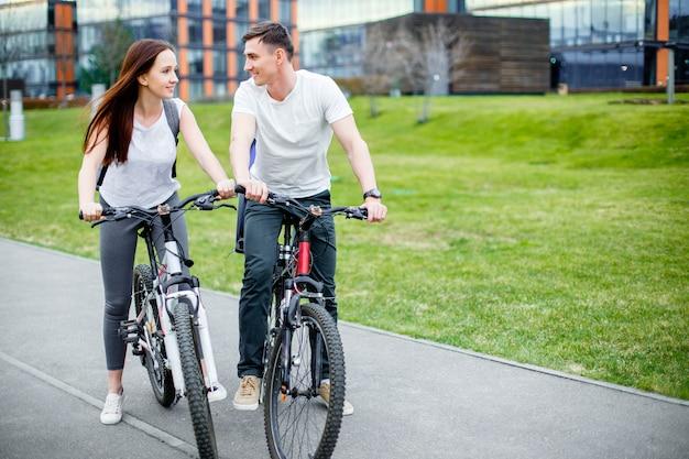 Jeune couple se promener à vélo par une journée ensoleillée dans la ville
