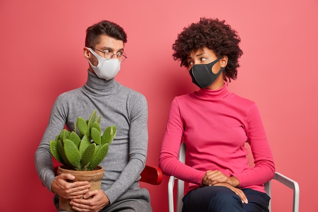 Jeune couple se regarde tristement porter des masques pendant la quarantaine à la maison poser sur des chaises éviter la contagion et rester en sécurité transporter des cactus en pot