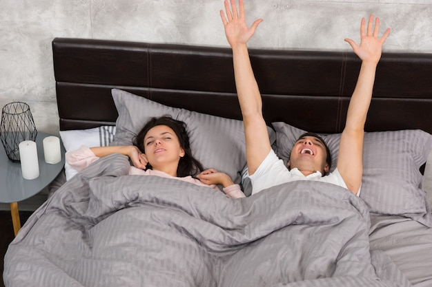 Jeune couple se réveille et s'étire en position couchée dans le lit, portant un pyjama dans la chambre de style loft avec des couleurs grises