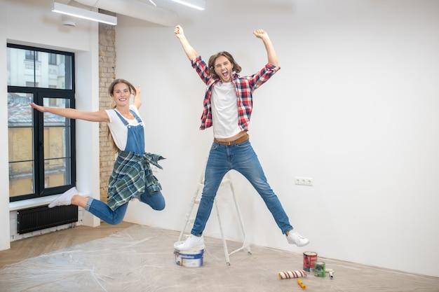 Jeune couple se sentant bien et sautant en l'air