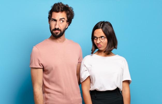 Jeune couple se sentant triste, bouleversé ou en colère et regardant sur le côté avec une attitude négative, fronçant les sourcils en désaccord
