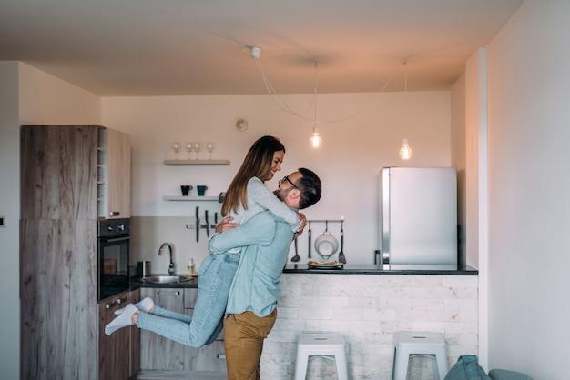 Jeune couple se sentir euphorique et s'amuser dans l'appartement.