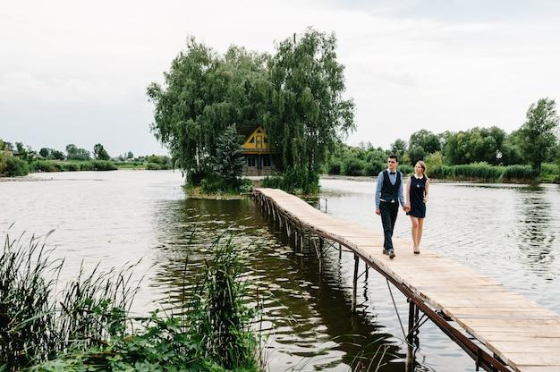 Le jeune couple se tient la main, va sur un pont en bois au-dessus du lac à la surface d'une vieille maison sur une île près d'arbres