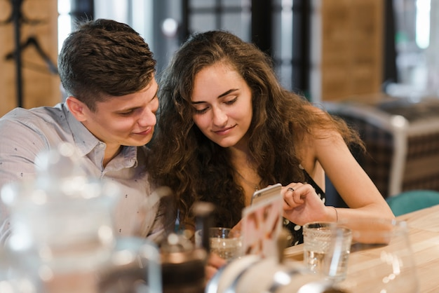 Jeune couple, séance, dans, barre, regarder, téléphone portable