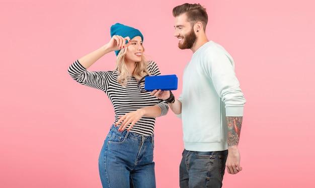 Jeune couple séduisant écoutant de la musique sur un haut-parleur sans fil portant une tenue élégante et cool souriante de bonne humeur positive posant sur le rose
