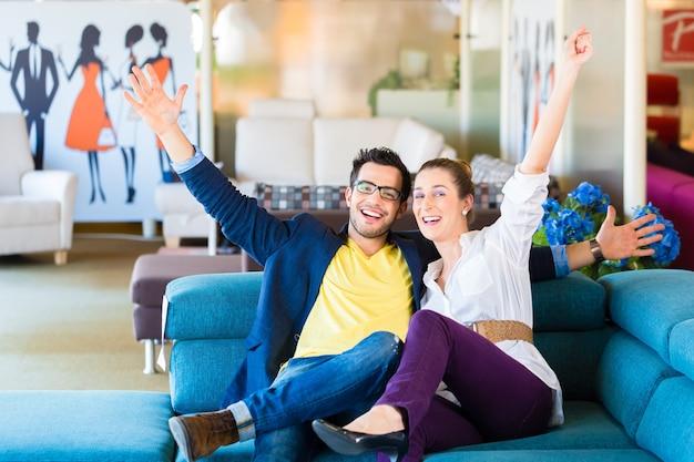 Jeune couple sélectionnant ensemble un canapé dans un magasin de meubles pour meubler la maison