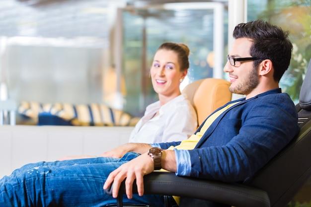 Jeune couple sélectionnant ensemble fauteuil dans un magasin de meubles