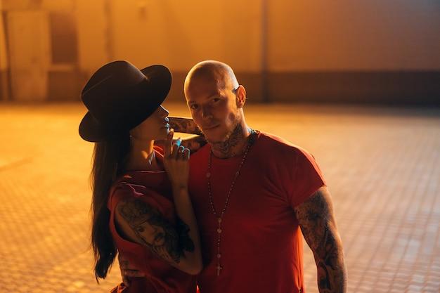 Un jeune couple sexy amoureux pose dans la rue de nuit de la ville.