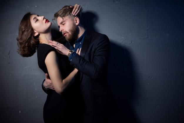 Un jeune couple sexy embrasse avec passion dans une pièce faiblement éclairée. portrait en gros plan.