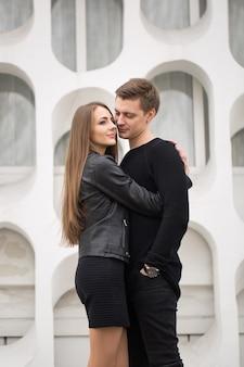 Jeune couple sexy en vêtements noirs posant avec un fond sur le mur blanc
