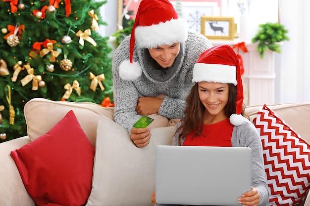 Jeune couple shopping en ligne avec carte de crédit à la maison pour noël