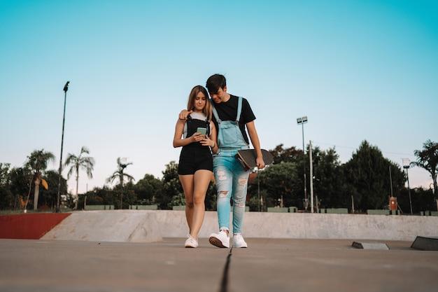 Jeune couple de skateboard appréciant passer du temps ensemble à une date au coucher du soleil.