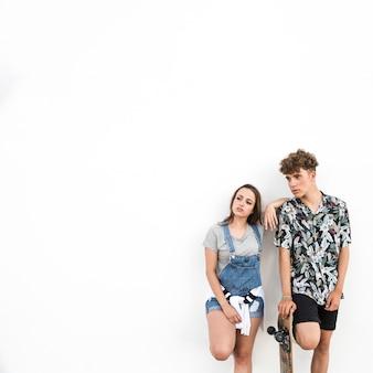 Jeune couple, à, skateboard, debout, contre, fond blanc
