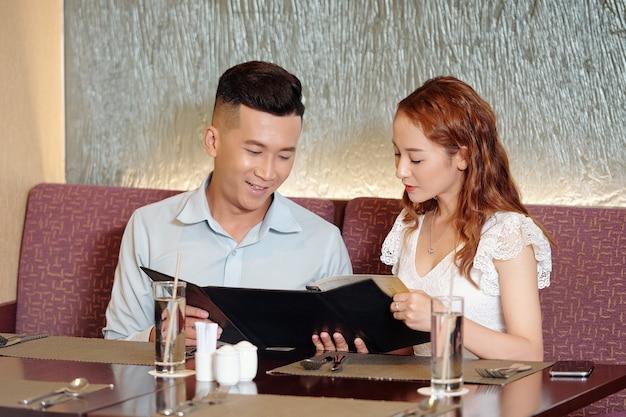 Jeune couple souriant amoureux lisant le menu ensemble lorsqu'il est assis à la table du restaurant