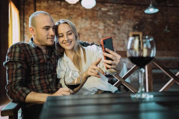Jeune couple souriant assis à une table de restaurant et prenant un selfie.