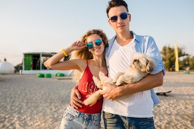 Jeune couple souriant attrayant s'amusant sur la plage en jouant avec le chien de race shih-tsu