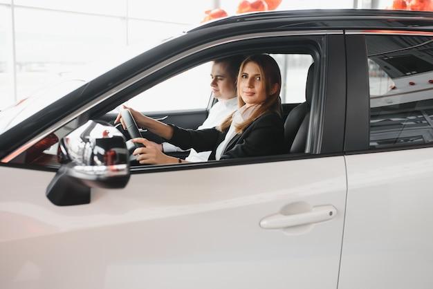 Jeune couple souriant au showroom automobile