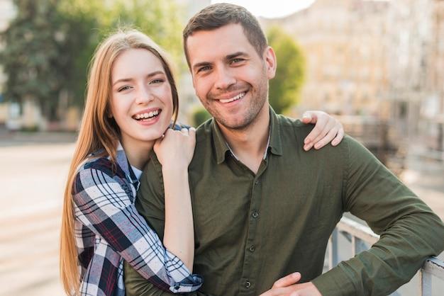 Jeune couple souriant, debout près de la rambarde, regardant la caméra