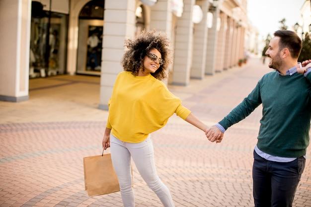 Jeune couple souriant, faire du shopping dans une rue urbaine