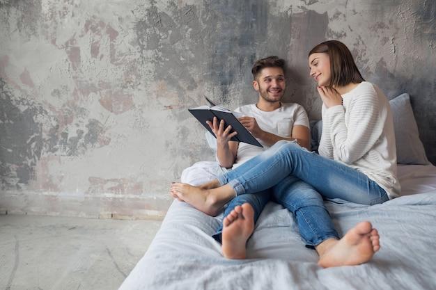 Jeune couple souriant heureux assis sur le lit à la maison en tenue décontractée, livre de lecture portant des jeans, homme et femme, passer du temps romantique ensemble