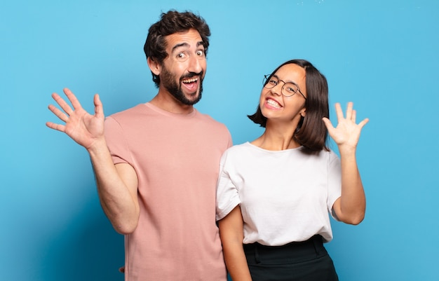 Jeune couple souriant joyeusement et gaiement, en agitant la main, en vous accueillant et en vous saluant, ou en vous disant au revoir