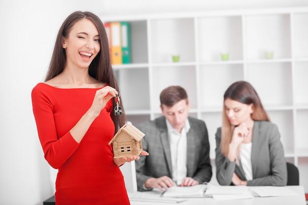 Jeune couple souriant sur le point de signer un contrat de location de maison
