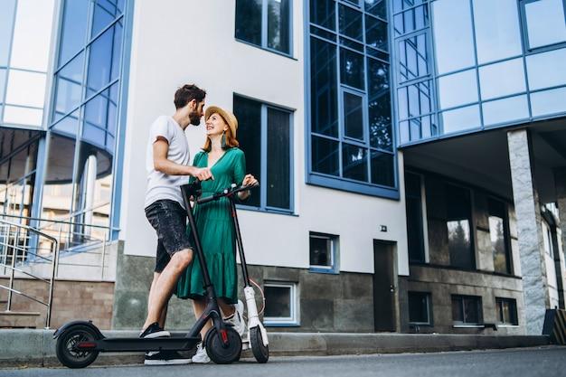 Un jeune couple souriant profite d'une promenade en ville sur des scooters électriques.