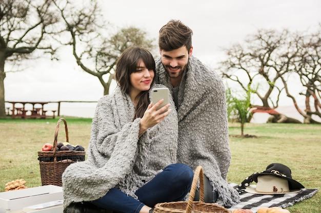 Jeune couple souriant, regardant un téléphone portable dans le parc
