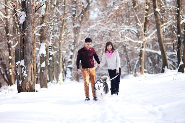 Jeune couple souriant et s'amusant dans le parc d'hiver avec leur chien husky.