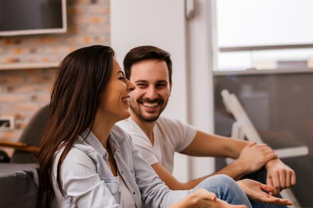 Jeune couple souriant et s'amusant à la maison