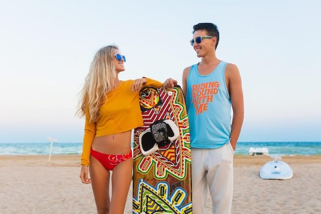 Jeune couple souriant s'amusant sur la plage avec planche de kite surf en vacances d'été