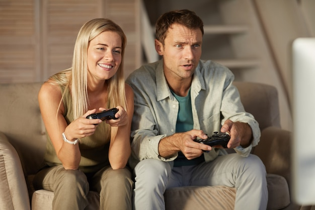 Jeune couple souriant s'amusant tout en jouant au jeu d'ordinateur à la maison