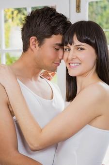 Jeune couple souriant et se faisant des câlins dans le salon