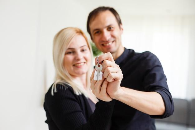 Jeune couple souriant tenant les clés de leur nouvelle maison