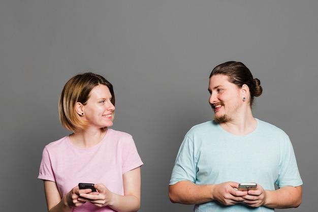 Jeune couple souriant tenant un téléphone portable à la main contre le mur gris