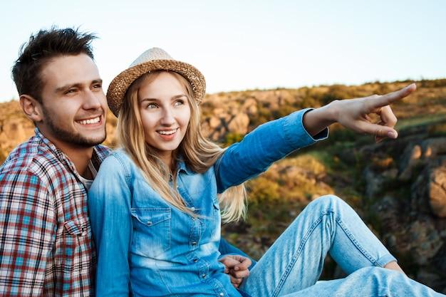 Jeune couple, sourire, séance, sur, rocher, dans, canyon, apprécier, vue